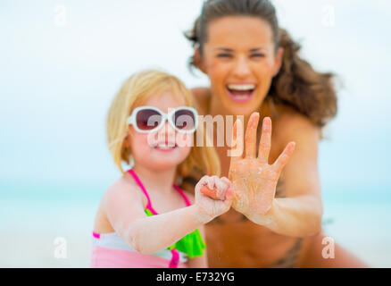 Closeup on baby girl holding mothers finger - Stock Photo
