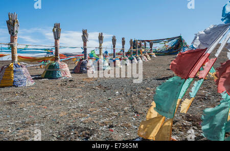 China, Tibet, Qinghai, Buddhist sacred religious place at the Tibetan mountain pass with a lot of waving colorful - Stock Photo