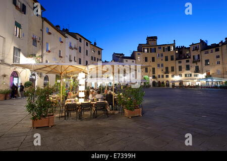 Restaurants in the evening in the Piazza Anfiteatro Romano, Lucca, Tuscany, Italy, Europe - Stock Photo