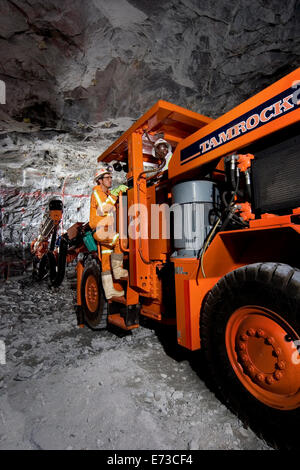 Placing Tamrock drill rig into position before drilling blast holes in underground rock face on platinum mine South - Stock Photo