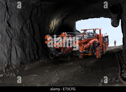 Drill rig moving down into platinum mine from entrance portal before drilling blast holes in rock for new service - Stock Photo
