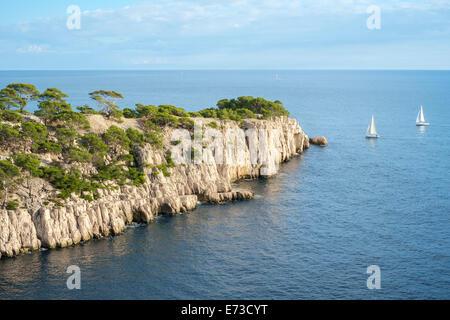 Sailboats passing the entrance of Calanque de Port-Pin - Stock Photo