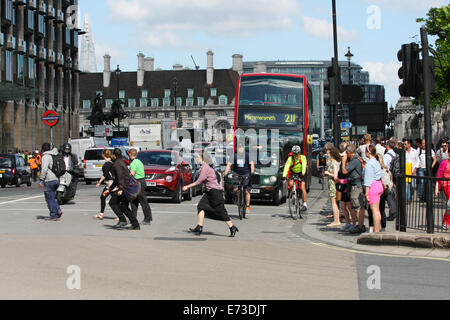 Pedestrians hurrying across a road in London as traffic starts to move after the traffic lights have turned green - Stock Photo