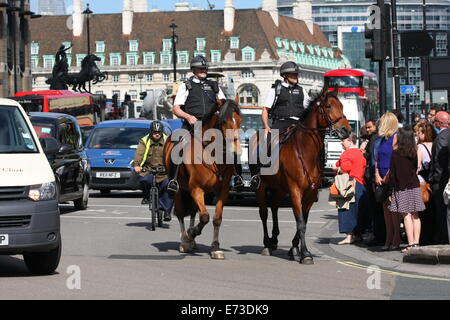 Traffic turning into Parliament Square in London, led by two police officers on horseback - Stock Photo