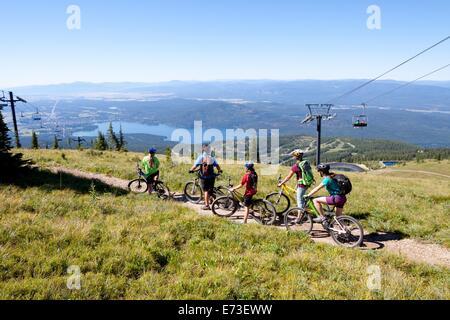 A family rides their bikes in Whitefish, Montana. - Stock Photo