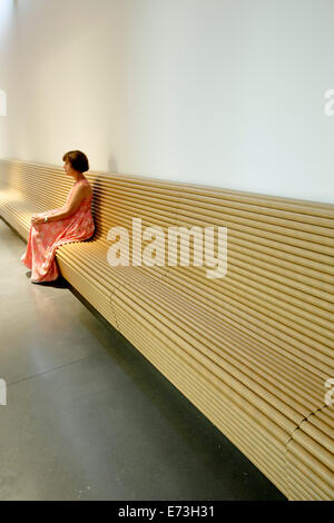 Woman sitting on bench made of cardboard tubes, Aspen Art Museum (by architect Shigeru Ban), Aspen, Colorado USA - Stock Photo