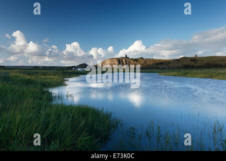 River Axe at Uphill with the Old Church of St Nicholas on the cliff-top. Somerset. England. UK. - Stock Photo