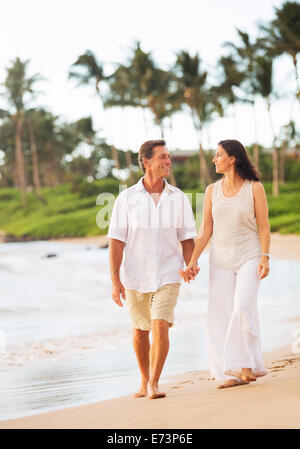 Romantic Mature Couple Enjoying Walk on the Beach - Stock Photo