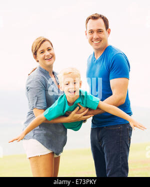 Happy Family Outside Playing Airplane with Young Son - Stock Photo