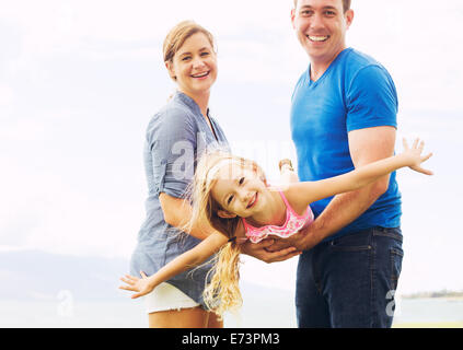Happy Family Outside Playing Airplane with Young Daughter - Stock Photo
