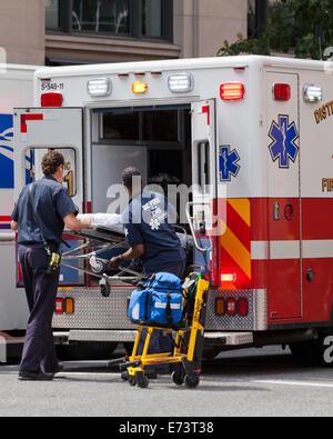 EMTs loading stretcher on EMS ambulance - Washington, DC USA - Stock Photo