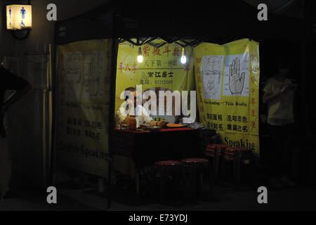Fortune teller in street stall. Kowloon, Hong Kong, China - Stock Photo