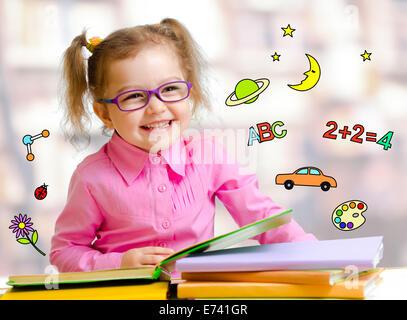 Happy child girl in glasses reading books in library - Stock Photo