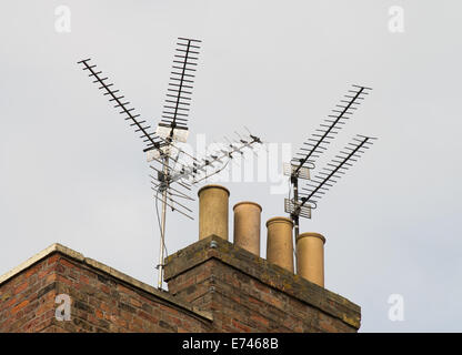 Multiple TV aerials with traditional chimney pots on roof Wisbech, Cambridgeshire, England, UK - Stock Photo