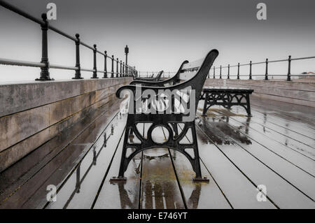 Empty Bench seats on the wet pier at Littlehampton in February - Stock Photo