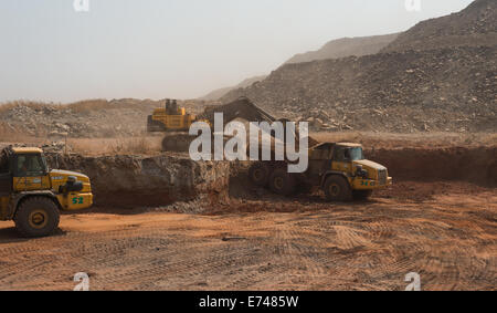 A Volvo excavator loads dirt into Bell mining trucks in an African open cast copper mine. - Stock Photo