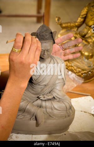 Eastern Bhutan, Trashi Yangtse, College, hands of art student sculpting Buddha figure in class - Stock Photo