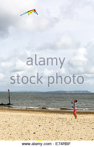 Boy flies kite on the beach at Mudeford - Stock Photo