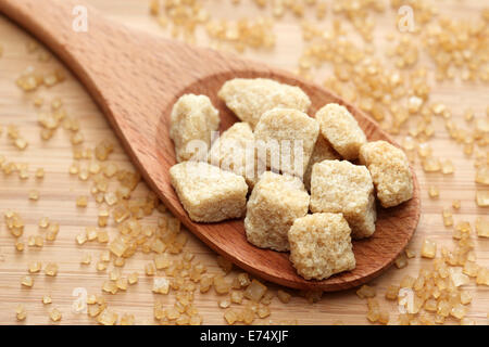 Brown cane sugar cubes in a wooden spoon. Close-up. - Stock Photo
