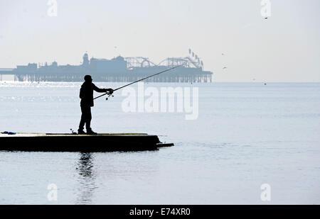 Brighton, Sussex, UK. 7th Sep, 2014. Weather: Fishermen cast their lines off Brighton beach in beautiful warm sunshine - Stock Photo