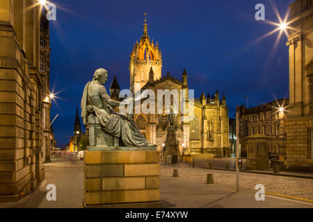 Twilight view down the Royal Mile with St. Giles Cathedral and statue of Scottish philosopher David Hume, Edinburgh, - Stock Photo