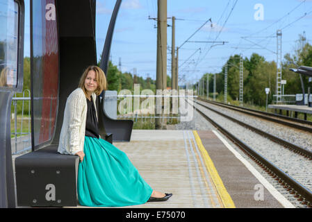 Young girl sitting on the railway station - Stock Photo