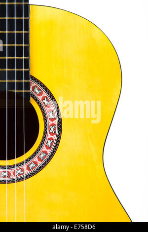 Detail view of yellow wooden classical acoustic guitar, isolated on white background.