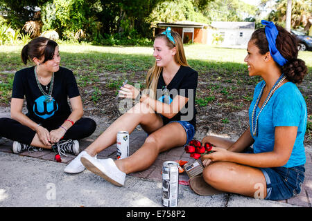 Three teenage girls sitting in the shade under a tree chatting - Stock Photo