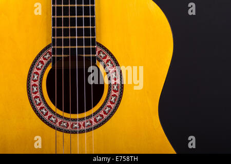 Front view of wooden classical acoustic guitar over black background. Stock Photo