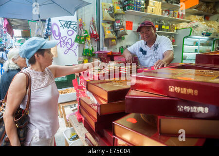 New York, USA. 7th September, 2014. A shopper in Chinatown in New York buys a box of mooncakes on Sunday, September - Stock Photo