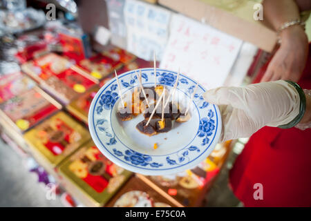 New York, USA. 7th September, 2014. A store in Chinatown in New York offer samples of their of mooncakes on Sunday, - Stock Photo