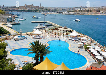 The swimming pool at the five star Luxury Grand Hotel Excelsior with views across Marsamxett Harbour - Stock Photo