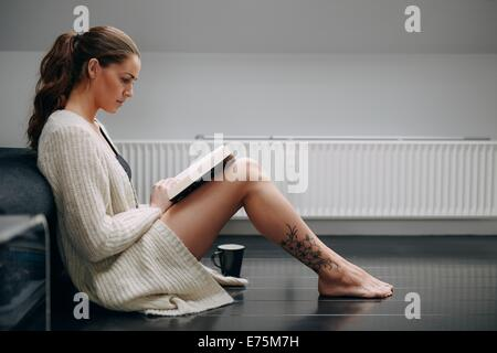 Side view of beautiful young lady reading a book. Caucasian female model at home sitting on floor by a couch with - Stock Photo