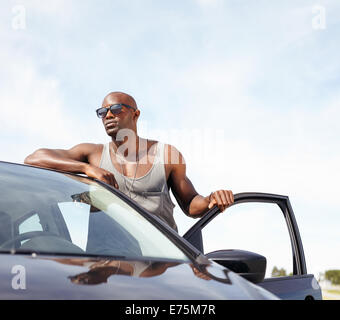 Portrait of smart young man leaning on car. African male model wearing sunglasses standing by his car looking away - Stock Photo