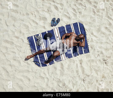 Top view of young guy lying shirtless on a mat reading a magazine. African male model relaxing on beach. - Stock Photo