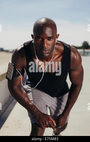 Fit young guy on his mark to start a run. Focused young male athlete outdoors looking at camera. Muscular African - Stock Photo
