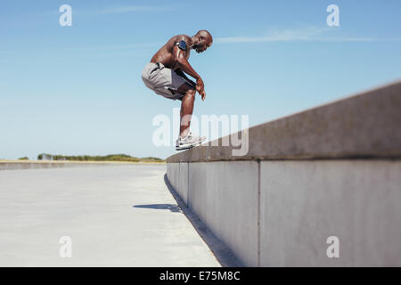 Image of shirtless young athlete jumping from a wall. African fitness male model doing jump exercise outdoors. - Stock Photo