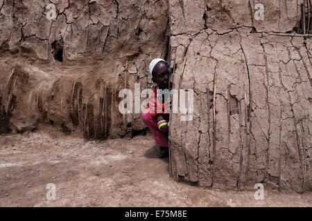 Maasai woman sits at the entrance to a traditional hut made from branches pasted with fresh cow-dung and mud which - Stock Photo