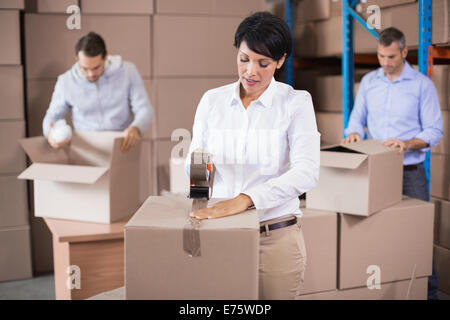 Warehouse workers packing up boxes - Stock Photo