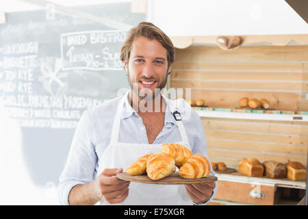 Handsome waiter holding tray of croissants - Stock Photo