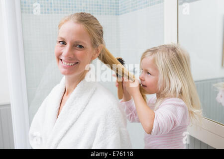 Happy mother and daughter brushing hair - Stock Photo