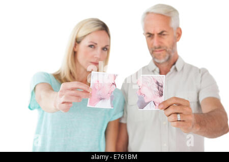 Couple holding two halves of torn photograph - Stock Photo