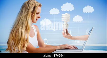 Composite image of pretty blonde using her laptop at the beach - Stock Photo