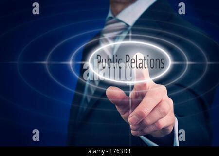 Businessman pressing a Public Relations concept button. - Stock Photo