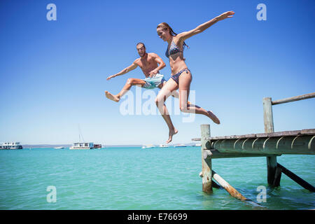 Couple jumping off wooden dock into water - Stock Photo