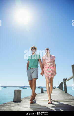 Couple holding hands walking along wooden dock - Stock Photo