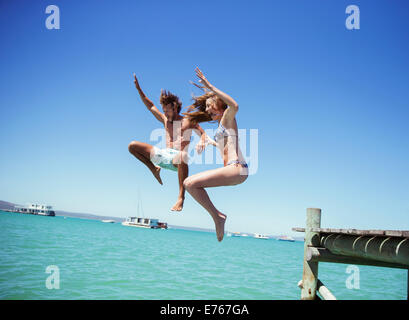 Couple jumping off wooden dock together - Stock Photo