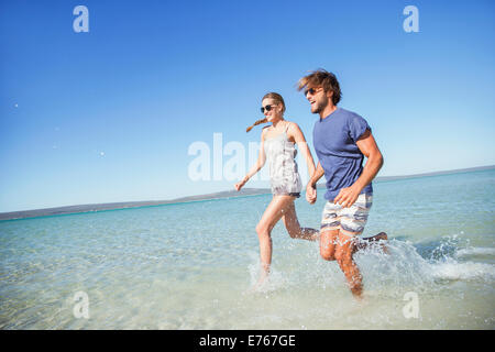 Couple running in water together - Stock Photo