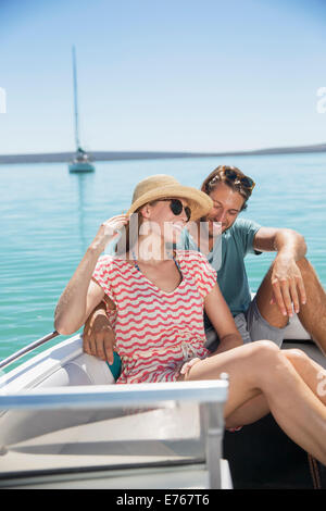 Couple sitting together in boat on water - Stock Photo