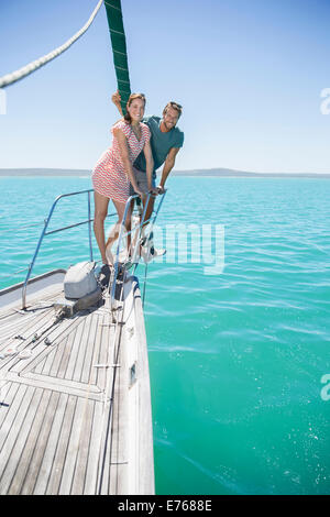 Couple standing on front of sailboat - Stock Photo